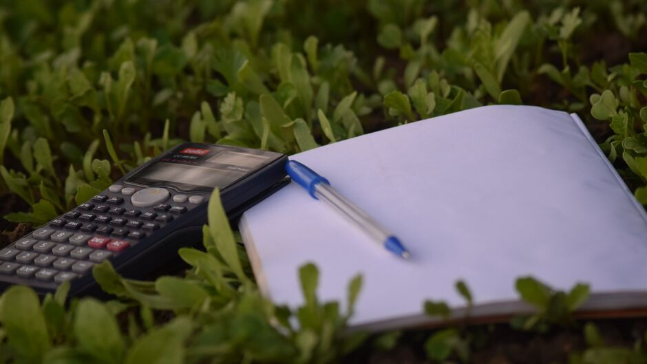 calculator and pad on grass